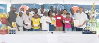 Representatives of the 18  participating local teams pose with the Tournament Booklets and cheques. (Orlando Charles Photo)