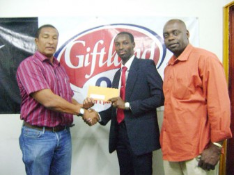 Giftland Office Max Marketing Manager, Compton Babb (centre), presents his company's sponsorship cheque to Kashif Muhammad as K&SO Co-Director Aubrey 'Shanghai' Major looks on.