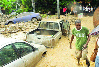 Vehicles, rocks and debris block the roadway yesterday after heavy rains sent torrents of muddy water through Saddle Road, Maraval. These three vehicles were pushed several feet away by flood waters.  (Trinidad Express photo)