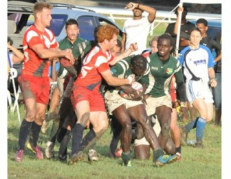 Guyana and Cayman Islands players battling for ball possession in the men's rugby final at a muddy Garrison Savannah yesterday.