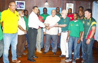 Minister of Sport Dr. Frank Anthony hands over the five million dollar cheque to President of the GRFU Kit Nascimento while President Donald Ramotar, GRFU executives and players of the men's rugby team look on. (Orlando Charles photo)