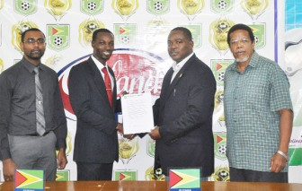 Giftland Officemax's Marketing Manager Campton Bobb (second left) and GFF President Franklin Wilson (ag) display the contract while CEO of Giftland Officemax CEO Eon Ramdeo (left) and GFF General Secretary Noel Adonis (right) look on.
