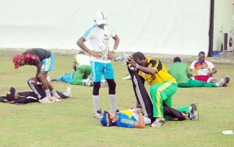 Trainer Orin Bailey gives Ramnaresh Sarwan a stretch as teammate Devendra Bishoo watches on. (Orlando Charles photo)
