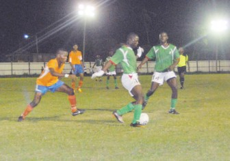 Action in the semi-final match between the Guyana Defence Force and Fruta Conquerors on Sunday night at the Tucville Playfield. (Orlando Charles photo)
