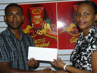 From left, Guyana Chess Federation's vice president, Irshad Mohammed, receives the sponsorship cheque from Almira Kassim, Marketing Assistant of Demerara Distillers Limited.