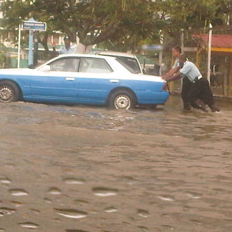 These policemen had to push this vehicle through deep waters in Eve Leary yesterday. (Treiston Joseph photo)