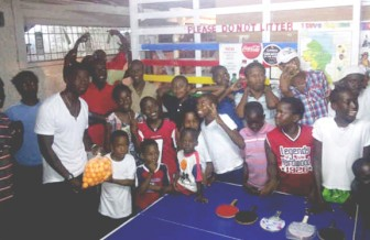 Former Caribbean junior boys champion,  Idi Lewis (left) presents the bag of balls to young Tyriq Saunders, while other members of the Rasville Youth Organization looks on appreciatively.