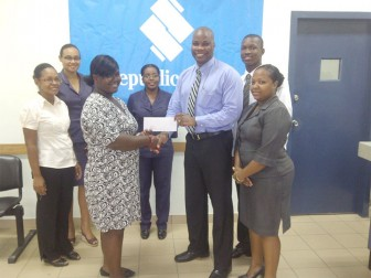 Republic Bank Limited, Linden Branch Manager Randolph Sears presents the sponsorship cheque to Dawn McCammon-Barker, reigning Caribbean Powerlifting Champion.