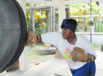 Heavyweight boxer Pauline London going hard on the tyre yesterday during her training session at the Andrew 'Sixhead' Lewis gym. (Orlando Charles photo)