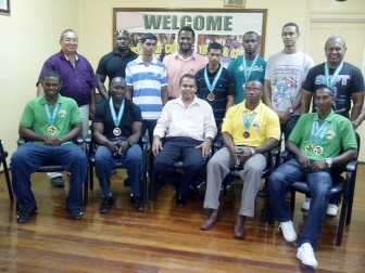 The successful powerlifting team poses for a photo opportunity with Minister of Sport Dr. Frank Anthony seated in the centre yesterday.