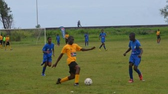 Action in the Tucville Secondary, Queen's College match yesterday at the Ministry of Education ground on Carifesta Avenue.
