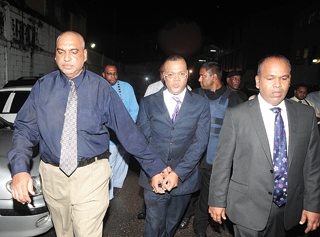 Ian Alleyne (centre) being escorted by a policemen (left) and his attorney (Trinidad Express photo)