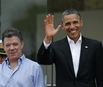President Barack Obama waves (R) while standing next to his Colombian counterpart Juan Manuel Santos after his arrival at the convention center where the Americas Summit is being held in Cartagena, April 14, 2012. Heads of state are meeting here from April 14-15. REUTERS/Enrique Marcarian
