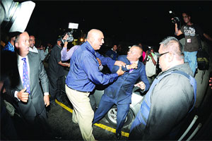 Assistant Superintendent Ajith Persad of the Port of Spain CID struggles to arrest Crime Watch host Ian Alleyne last night at Express House carpark in Port of Spain. Alleyne, it was said, was wanted for questioning in an alleged criminal matter in relation to a video showing the rape of a minor on Crime Watch last October.(Trinidad Express photo)