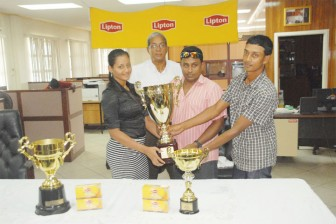 Everest skipper Troy Gonsalves (right) and GYO's Surendra Hiralall receive the Lipton Tea Cup from Alicia De Abreu, while Chief Executive Officer of De Sinco Group of Companies Frank De Abreu (at back) looks on.