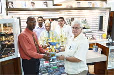 Dr. Jose Da Silva, Managing Director of Modern Optical presents the championship trophy to Ryan Sampson, Secretary of the GNRA while officials of the two organizations look on.