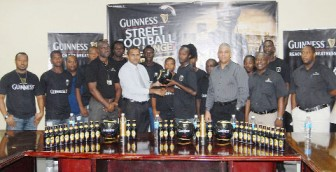 Minister of Sport Dr. Frank Anthony presents a game ball and other gear to one of the Team Guyana (Back Circle) players after the launching of the inaugural Guinness Caribbean Street Football Challenge yesterday in the boardroom of Banks DIH Limited, Thirst Park. (Orlando Charles photo)