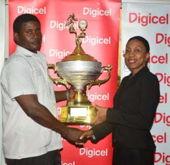 Lyndon Wilson (left) receives the first place trophy for the Police Sports Club