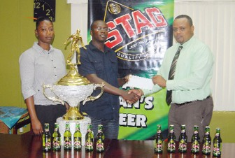 Marketing Manager of ANSA McAL, Troy Cadogan (right) hands over a sponsorship cheque to Secretary of the West Demerara Football Association, Adrian Giddings as the Assistant Secretary/ Treasurer of the association Chevon Monchoir looks on. (Orlando Charles photo)
