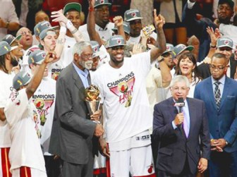 NBA great Bill Russell (L) prepares to present the Bill Russell NBA Finals MVP trophy to Miami Heat's LeBron James (C) after Game 5 of the NBA basketball finals against the Oklahoma City Thunder in Miami, Florida last night. REUTERS/Andrew Innerarity