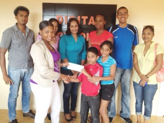 Chief Financial Officer of Digital Technology, Sabrine Sukhu, centre and other staff members witness the presentation of the sponsorship cheque by Customer Representative, Joneeka Fernandes, to young Niron Bissu whose mother is at right.