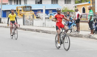 Robin Persaud crosses the finish line ahead of reigning junior road race champion and club mate Raynauth Jeffrey to capture this year's ninth annual National Milling Company (NAMILCO) Caricom 'Wheat-up' Cycle Road Race yesterday. (Orlando Charles photo)