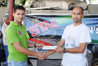 Ansa McAL on board: Stag Beer Brand Manager John Maikoo (left) renewed Ansa McAL's sponsorship to Ryan Rahaman for the third successive year yesterday. Rahaman and his Ford Sierra will be competing in the Group Four races tomorrow when the second National Race of Champions event for 2012 is staged at the South Dakota Circuit. (Orlando Charles photo)