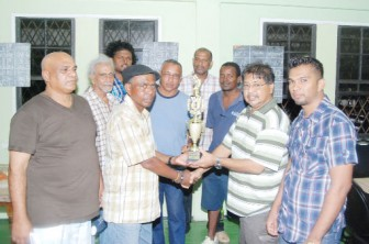 Captain of International Six Manniram 'Packer' Shew receives the winning trophy from sponsor Soomdat 'Rico' Jeet while his team mates look on.