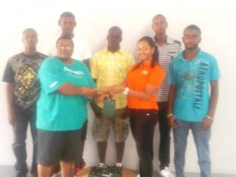Ann Gordon (left) receives donations from Alicia DeAbreu in the presence of some of Kwakwani's team member in the background. (Treiston Joseph photo)