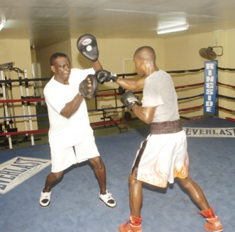 Local featherweight champion Clive 'Wonder Kid' Atwell attacking the pads of trainer Lennox Daniels yesterday during his training session at the Andrew 'Sixhead' Lewis Gym ahead of Friday night's ring date with Revlon Lake. (Aubrey Crawford photo)