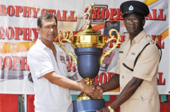 For the Champion Division: Proprietor of the Trophy Stall, Ramesh Sunich (left) yesterday presented the Champion Division Trophy to  Assistant Superintendent of Police and Games Officer, Colin Boyce. The trophy will go to the Division winner in this year's 58th edition of the GPF annual athletic championships which commenced on Sunday and concludes on Friday at Eve Leary Ground.