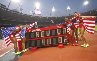 Members of the U.S. team pose with their national flags after winning the women's 4x100m relay final during the London 2012 Olympic Games REUTERS/KAI PFAFFENBACH