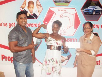 In photo, Alisha Fortune, shows off her biceps whilst receiving the sponsorship cheque from Andrea Jodhan-Khan, Marketing Co-ordinator of the Hand-in-Hand company as Videsh Sookram, general secretary of the GABBFF, looks on.