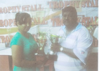 Chitra Harilall, of the Trophy Stall hands over the trophies to Jiaram, president of the Guyana Draughts Association.