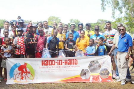 Winners and runners-up pose with prizes at the completion of yesterday's eighth annual Hand-in-Hand Insurance cycling programme at the National Park. (Orlando Charles photo)