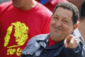 Venezuela's President Hugo Chavez gestures as he arrives to cast his vote for the presidential elections in Caracas