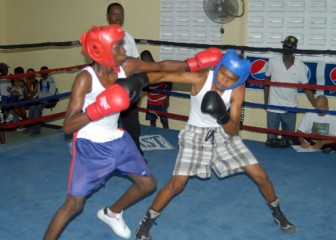 Shaka Moore of the Essequibo Boxing Gym (left) throws a jab during action in his three-nil victory over FYF's, Junior Henry, in their highly entertaining bout yesterday at the Andrew 'Sixhead' Lewis Gym. (Orlando Charles photo)