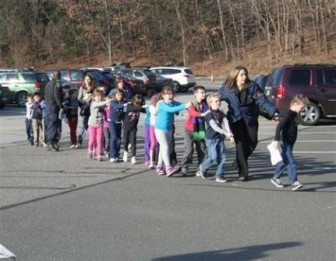 State police personnel lead children from the Sandy Hook Elementary School in this handout picture from the Newtown Bee, in Newtown, Connecticut, December 14, 2012. All public schools in Newtown, Connecticut, were placed in lockdown on Friday following a shooting at Sandy Hook Elementary School. REUTERS/Newtown Bee/Shannon Hicks/Handout