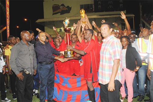 MVP of the 23rd Kashif and Shanghai Tournament and Captain of Buxton United, Dwain Jacobs, collects the champion's trophy from Minister of Sport, Dr. Frank Anthony after his side defeated Amelia's Ward in a penalty shootout at the Providence National Stadium on New Year's Day. (Aubrey Crawford photo)