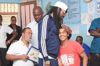 Beenie Man embracing 18-year-old Anil after his presentation while 53-year-old Rudolph (left) looks on. (Arian Browne photo)