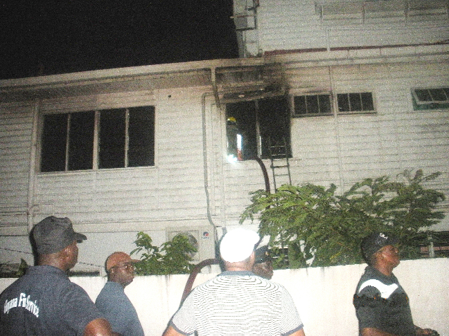 The window to the office that was broken to gain access to the building. In the compound of the building east of the ministry, firefighters watch on as Fire Chief Marlon Gentle (right ) directs his troops.