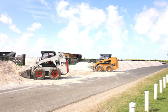 Two bobcats transferring sand piled on the University of Guyana Road into the Specialty Hospital compound