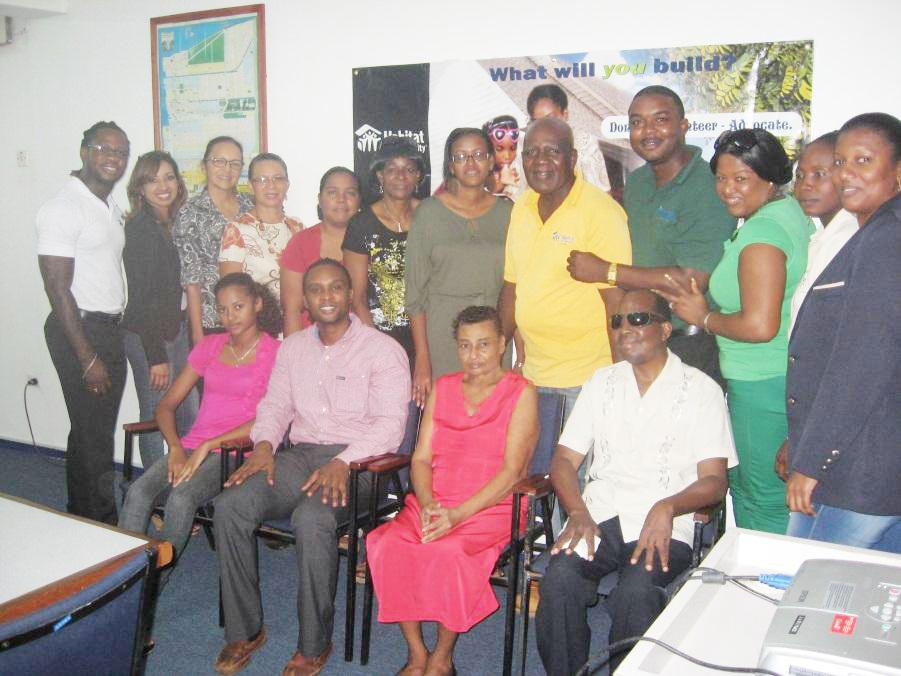 National Director, HfHG, Rawle Small (seated-second left); home owner, Kamanie Chichester (seated – third left), sponsors of the Buy-a-Block 2012 initiative; and HfHG staff. (Habitat photo)