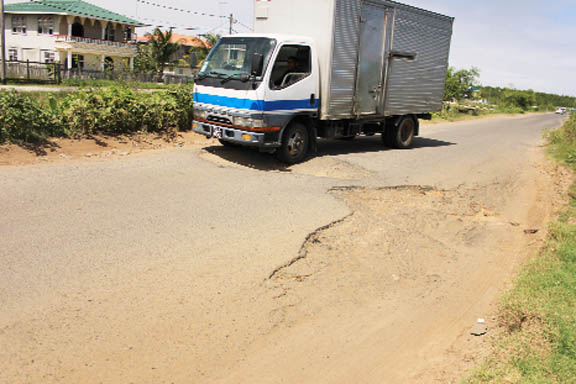 A truck trying to navigate its way through the Bee Hive main access road, East Coast Demerara.