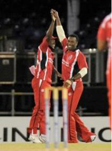 Darren Bravo (left) and Kieron Pollard celebrate as T&T charge to victory. (Photo courtesy WICB)