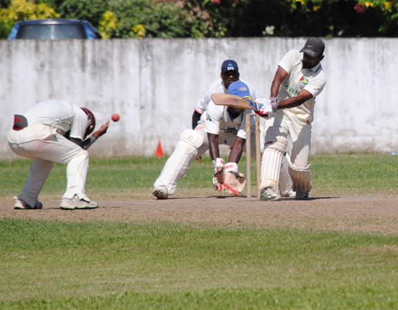 The fielder at forward short leg tries to take evasive action as century maker Sewnarine Chattergoon attempts to punish a short delivery. (Aubrey Crawford photo)