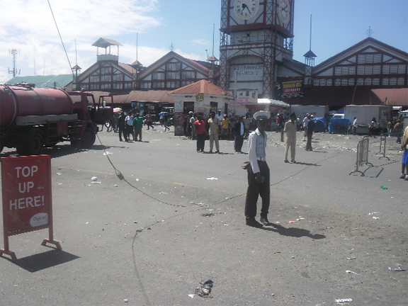 Policemen stand around the guy wire near Stabroek Square after it was disconnected from its power source. (Javone Vickerie photo)  See story on page 2