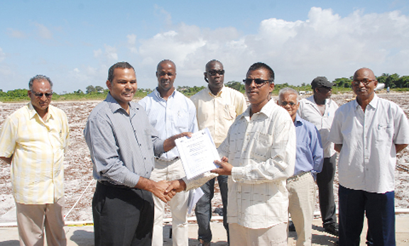 Minister of Sport, Dr. Frank Anthony yesterday awarding one of the sub lot contracts to a Bholonauth Contracting and Engineering Services repreasentative.