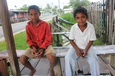 Two children relaxing under a local shop