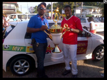 Aubrey Major Jr. on behalf of the Kashif and Shanghai Organization, formally presents the champions' trophy and the keys to the motor vehicle to Buxton United's captain, Dwain Jacobs.